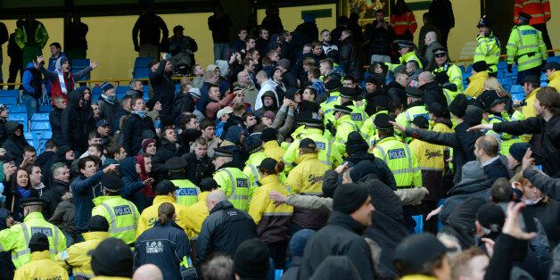 Police and stewards separate opposition supporters during the English Premier League football match between...