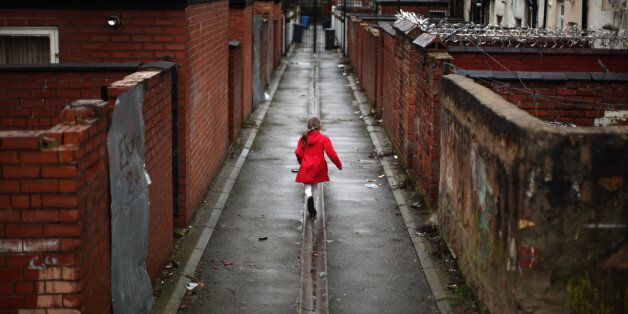 A young girl spends the half term school holiday playing in an an alleyway in the Gorton area of