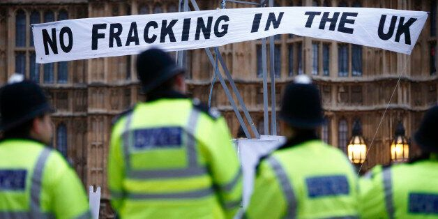 British police secure the area where demonstrators erected a mock fracking rig with a banner reading...