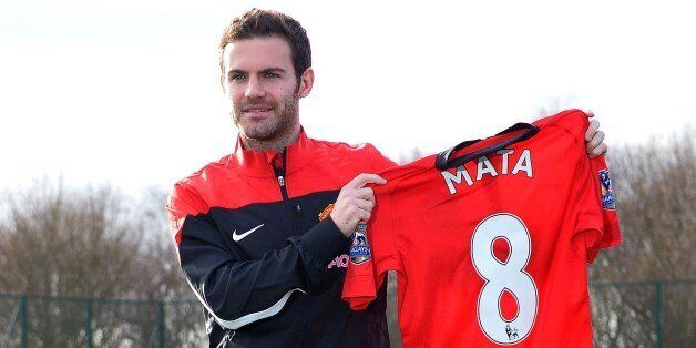 Manchester United's new signing, Spanish midfielder Juan Mata, poses with a team jersey at the club training...