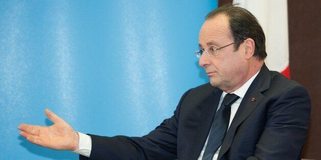 French President Francois Hollande gestures as he speaks during a meeting with British Prime Minister...