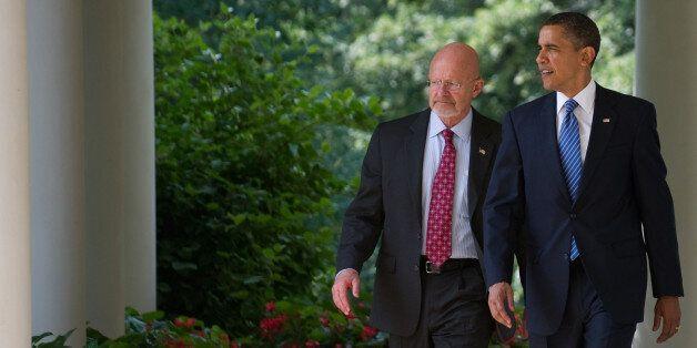 US President Barack Obama walks back down the West Wing Colonnade alongside retired General James Clapper,...