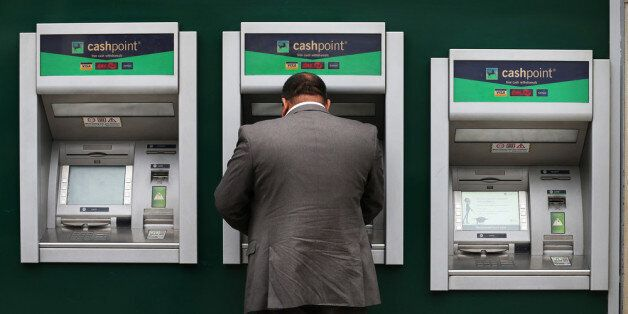 LONDON, ENGLAND - SEPTEMBER 17: A customer uses a cash machine at Lloyd's Bank branch on September 17,...