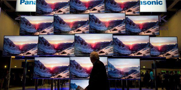 A fairgoer walks past a display of Panasonic Smart Viera 4K ultra HD Televisions at the Panasonic stand...