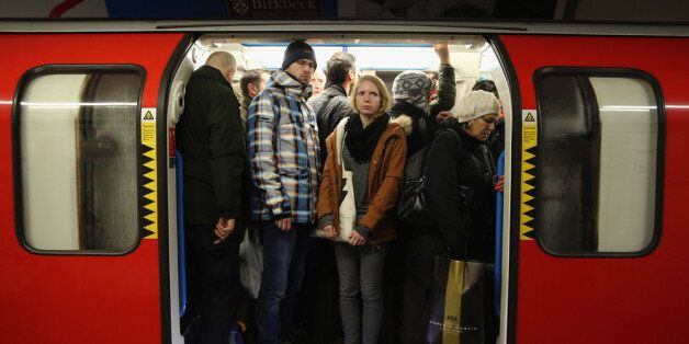 LONDON, ENGLAND - FEBRUARY 05: Commuters crowd on to a tube at Oxford Street station on February 5, 2014,...