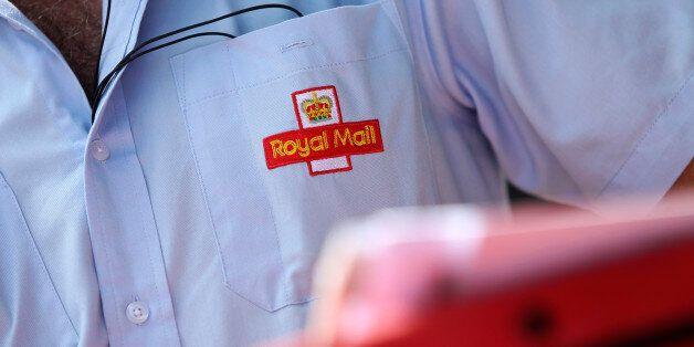 An embroidered logo sits on the shirt pocket of a Royal Mail Group Ltd. postman as he delivers mail in...