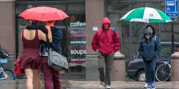Office workers and tourists are pictured in the rain outside St Paul's cathedral in central London this