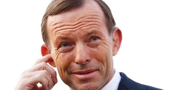 Tony Abbott, Australia's opposition leader, adjusts his earpiece before a television interview outside...