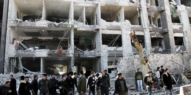 Syrian security officers gather in front the damaged building, attacked by al-Qaida-style group Jabhat...