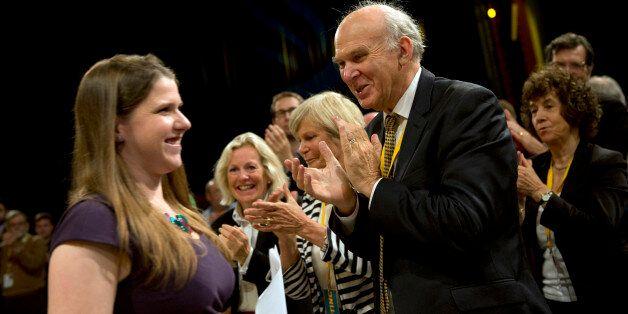 British Business Secretary Vince Cable (R) applauds as Jo Swinson (L), Parliamentary Under-Secretary...