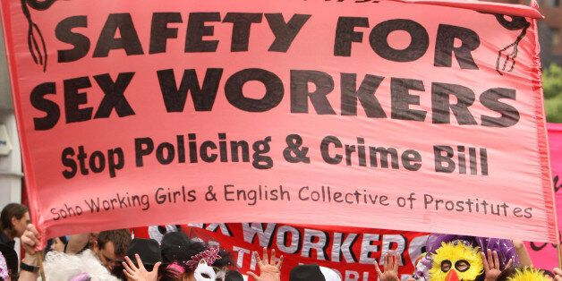 A masked parade of sex workers and supporters, take part in a parade, in Soho, London in an event to...