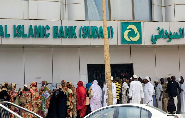 Sudanese customers queue to access money services at the Faisal Islamic Bank  in Khartoum on June...