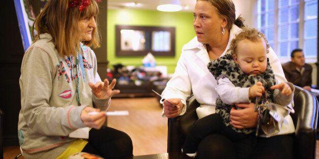 LIVERPOOL, ENGLAND - DECEMBER 21: Foodbank volunteer Linda Wilson (L) talks to Elaine Oliver and her...