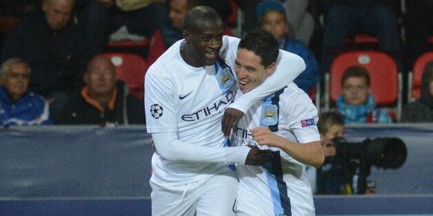 Manchester City's Ivorian midfielder Yaya Toure (L) celebrates with his teammate French midfielder Samir...