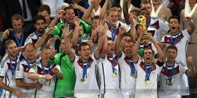 Germany's forward Mario Goetze (R) celebrates with teammates after scoring during the final football...