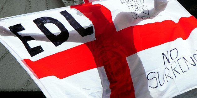 A man holds a flag during a EDL march at Centenary Square in