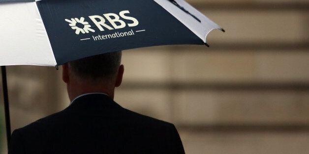 A pedestrian carries a Royal Bank of Scotland Group Plc (RBS) branded umbrella in London, U.K., on Friday,...