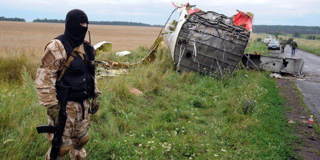 An armed pro-Russia militant stands guard at the site of the crash of a Malaysian airliner carrying 298...