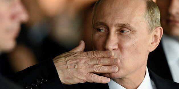 Russian President Vladimir Putin gestures while leaving the BRICS-UNASUR Summit at Itamaraty Palace in...