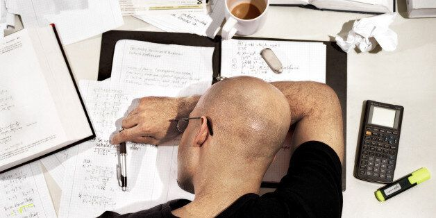 Young man with head down on desk covered in text books and