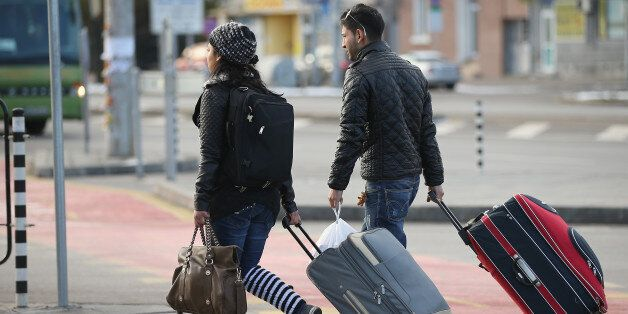 SOFIA, BULGARIA - DECEMBER 07: A young Roma couple walk with suitcases outside the main bus station on...