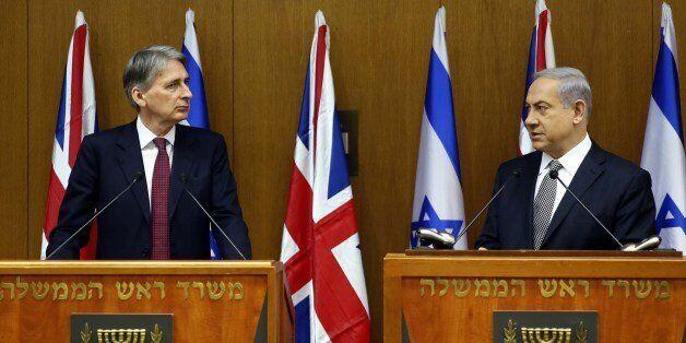 Israeli Prime Minister Benjamin Netanyahu (R) and British Foreign Secretary Philip Hammond hold a joint...