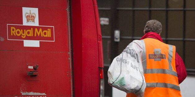 A Royal Mail Group Ltd. employee carries a mail sack towards a postal truck in London, U.K., on Friday,...