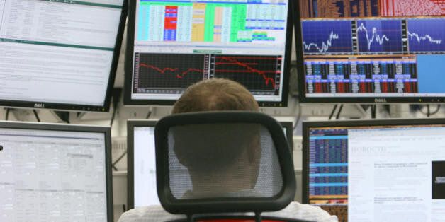 A Russian trader studies markets at a private international investment banking firm in Moscow on October...