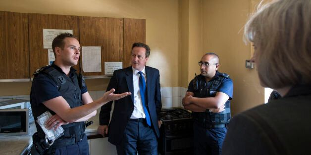 Prime Minster David Cameron (second left) and Home Secretary Theresa May (right) speak to Home Office...
