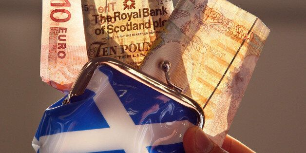 A posed photo of an Euro, a Royal Bank of Scotland and a Bank of England note being pulled from a Saltire...
