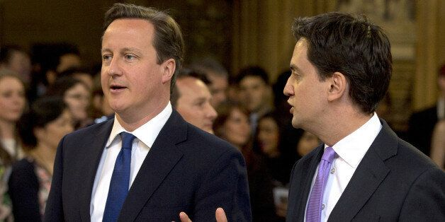 British Prime Minster David Cameron (L) and Ed Miliband, the Leader of the Labour Party, walk through...