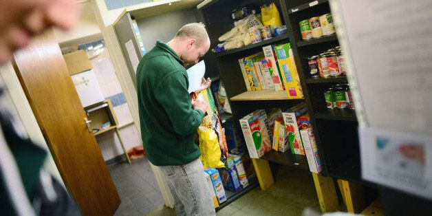 WHITBURN, SCOTLAND - MARCH 07: A Stuart Little volunteer packs food at a food bank on March 7, 2014 in...