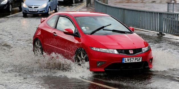 Cars pass through a flash flood following a heavy rain shower in Maidstone,