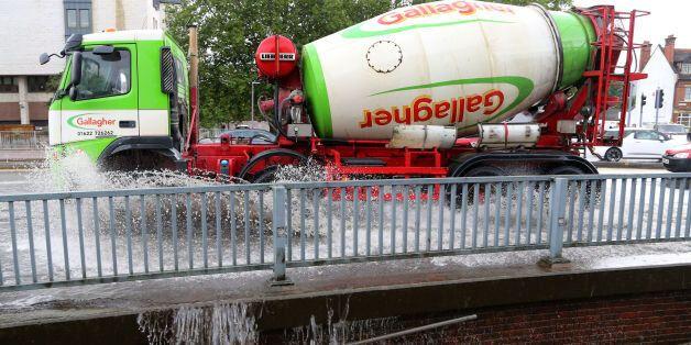 A lorry passes through a flash flood following a heavy rain shower in Maidstone,