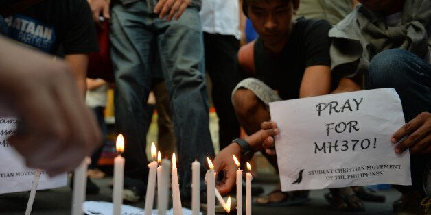 Students light candles as they hold placards in solidarity with families of the passengers of the missing...