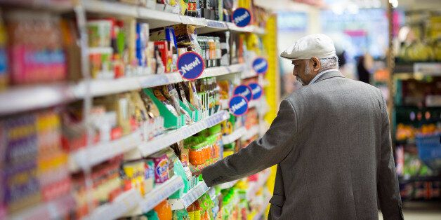 A customer looks at the price of an item displayed for sale on a shelf inside a Tesco Metro