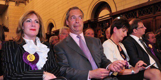 UK Independence Party (UKIP) leader Nigel Farage (2L) sits with fellow UKIP candidates Janice Atkinson...