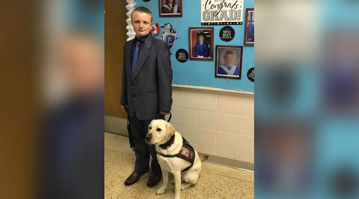 Cameron Cadarette is seen at school with his service dog, Vincent.