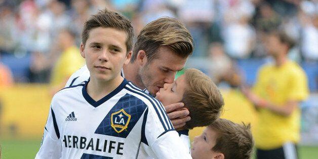 CARSON, CA - DECEMBER 01: David Beckham #23 of Los Angeles Galaxy kisses his sons Brooklyn, Romeo and...