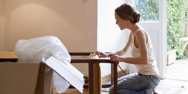 Woman taking apart furniture ready for moving