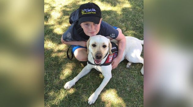 Cameron Cadarette poses with his service dog,