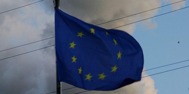 BERLIN - MARCH 19: An European (EU) flag seen near the smoking power plant in Berlin Spandau on March...