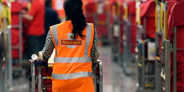 A Royal Mail Plc employee pushes a trolley of un-sorted parcels through the sorting area at the company's...