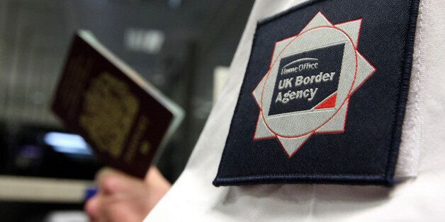 File photo dated 23/11/2009 of a UK Border Agency officer checking a passport as Britain is at risk of...