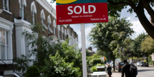 LONDON, ENGLAND - JUNE 03: An estate agent sold sign is displayed outside a property on June 3, 2014...