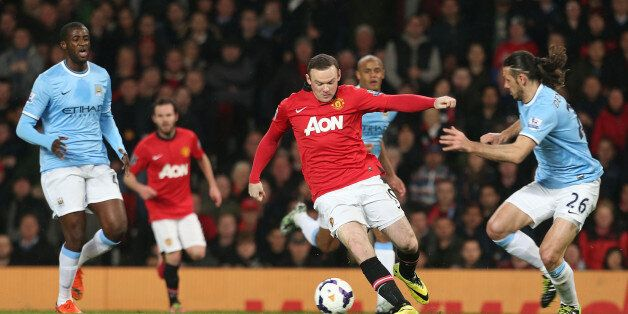 MANCHESTER, ENGLAND - MARCH 25: Wayne Rooney of Manchester United in action with Martin Demichelis of...