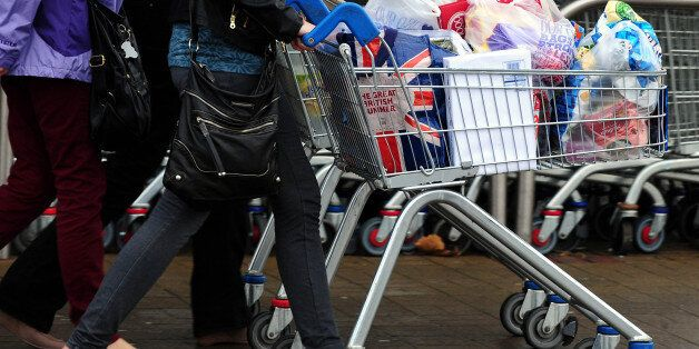 File photo dated 31/12/13 of customers with their shopping leave a Tesco store as Britain's biggest supermarket...