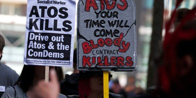 Protesters carry placards during a protest against multinational IT firm and Paralympics sponsor Atos...