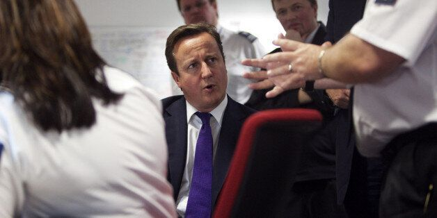 LONDION - OCTOBER 10: Prime Minister David Cameron talks to UK border agency officials in their control...