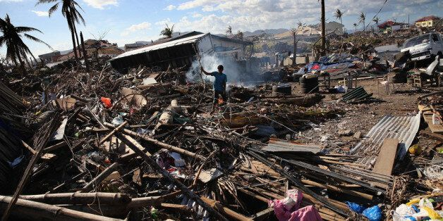 LEYTE, PHILIPPINES - NOVEMBER 15: A man sifts through debris on November 15, 2013 in Leyte, Philippines....